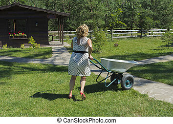 Woman with wheelbarrow on the lawn near a private house