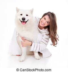 woman with white dog, smiling - a studio image of a young...