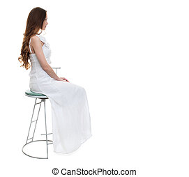 woman with white dress sitting on chair in studio