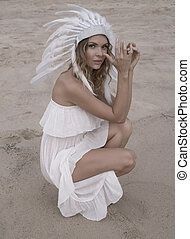 Woman with white feather indian hat at the beach