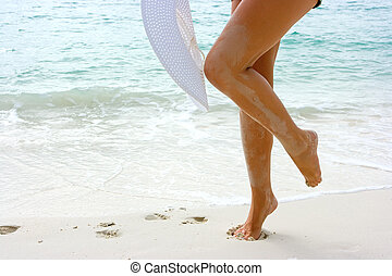 Woman with white hat on the beach