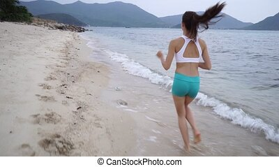 Woman with white top running on the beach.
