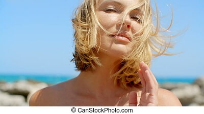 Woman with Wind Blown Blond Hair by Ocean - Head and Bare...