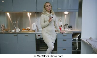 Woman with wine standing in kitchen