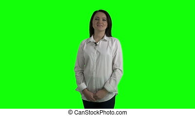 Woman with wireless lavalier microphone talking to camera against a green screen
