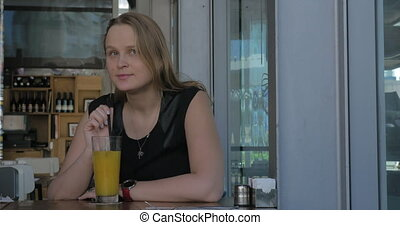 Woman with wistful look having juice in cafe - Cinemagraph -...
