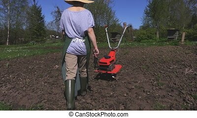 Woman with wrenches near cultivator