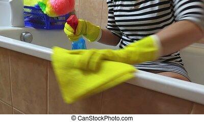 Woman with yellow rag polishing the edge of bath