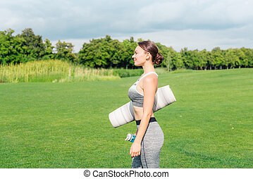 woman with yoga mat and water bottle