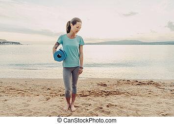 Woman with yoga mat walking on beach.