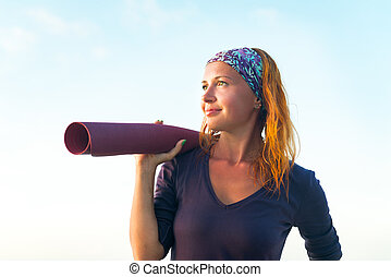 Woman with yoga mat - Young woman with long red hair and ...