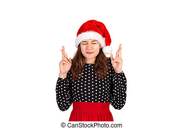 woman withclosing eyes and raising crossed fingers while praying and hoping from dream come true. emotional girl in santa claus christmas hat isolated on white background. holiday concept