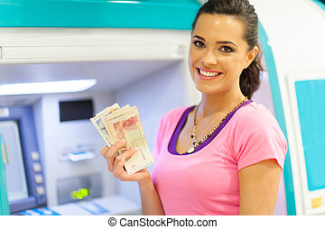 woman withdrawing cash at an ATM - happy young woman...