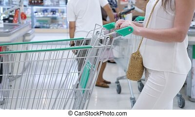 Woman without face in a white suit with a trolley in a store...