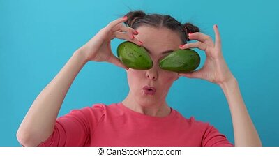 Smiling girl covering his eyes with Avocado. Happy girl with fresh vegetables wonders. Close up girl fool around at camera