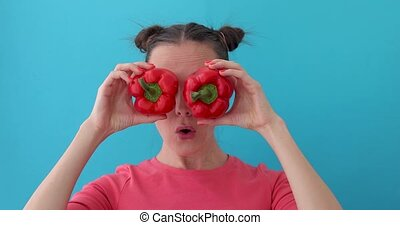 Smiling girl covering his eyes with paprika peppers. Happy girl with fresh vegetables wonders. Close up girl fool around at camera