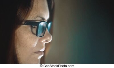 Woman work a at night woman reflection glasses computer...