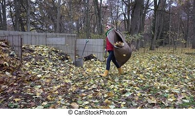 woman work in backyard. Dry leaves compost pile in autumn....