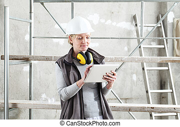 woman worker builder work with digital tablet, wearing helmet and hearing protection headphones , on scaffolding construction site indoors background