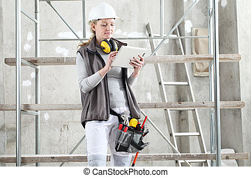 woman worker builder work with digital tablet, wearing helmet, hearing protection headphones and bag tools, on scaffolding construction site indoors background