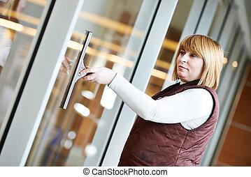 woman worker cleaning indoor window - woman cleaner worker...