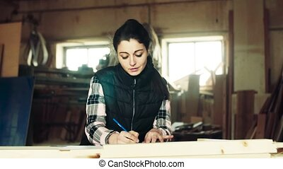 Woman worker in the carpentry workshop, making plans.