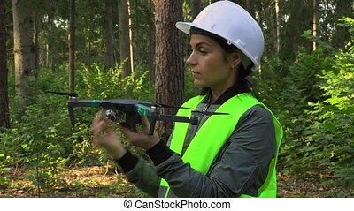 Woman Worker prepares Drone Quadcopter for video forest ...