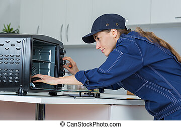 woman worker repairing oven appliance in kitchen room