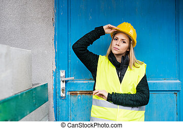 Woman worker standing outside a warehouse.