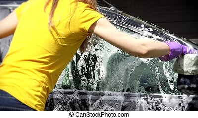 Woman worker washing car with sponge on a car wash - Closeup...