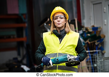 Woman worker with angle grinder in a warehouse.