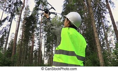 Woman Worker with Drone Quadcopter before take off in forest...