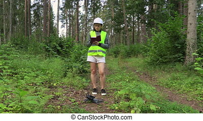 Woman Worker writing near Drone on forest path after forest ...