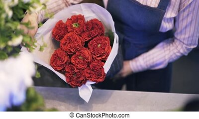 Woman working as a florist adjusting the wrapping paper on a bunch of roses