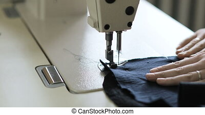woman working as fashion designer with sewing machine in studio