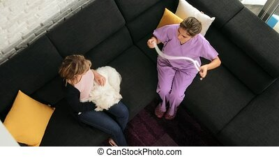 Woman Working As Veterinary Visiting Dog During House Call -...