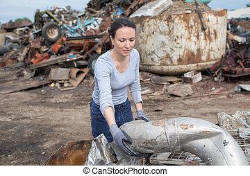 woman working at a junkyard