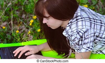 Woman working at a laptop lying on the meadow