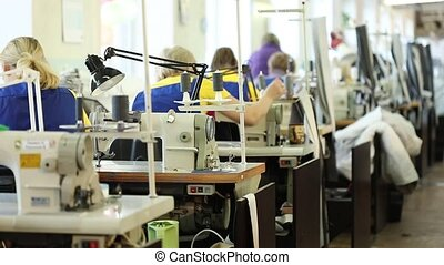 Woman working at a sewing machine, Industrial size textile factory, workers on the production line, industrial interior, needle sewing machine, shallow depth of field