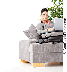Woman working at home - Young woman sitting on couch working...