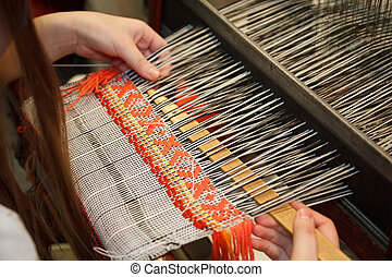 Woman working at the loom. Russian national crafts. Focus on the fabric.