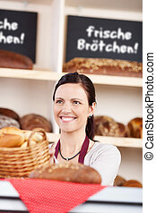 Woman working behind a counter in a bakery