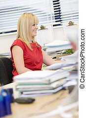 Woman working happily at her desk
