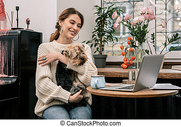 Woman working in a cafe with her dog
