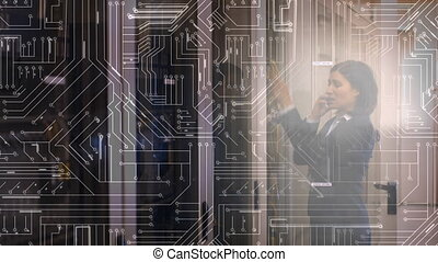 Woman working in a server room on the phone with glowing circuit board in foreground
