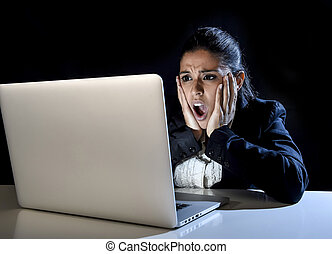 woman working in darkness on laptop computer late at night surprised in shock and stress