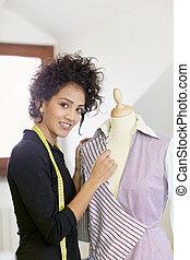 Woman working in fashion design studio - Young hispanic...
