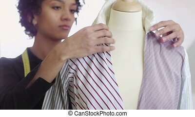 Young hispanic female dressmaker adjusting clothes on tailoring mannequin and smiling at camera.