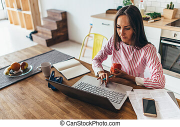 Woman working on a laptop while sitting at the table at home