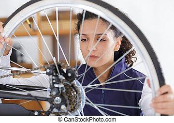 woman working on bike wheel